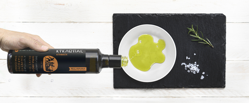 A hand pouring olive oil from a Kyklopas bottle onto a white plate