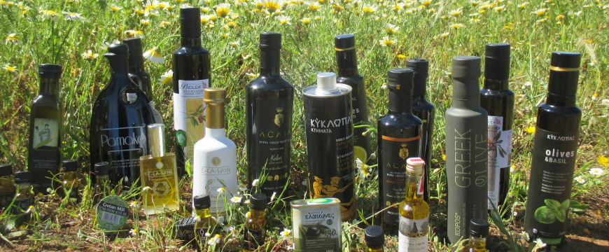 many bottles of Greek olive oil outside, in front of a field of daisies