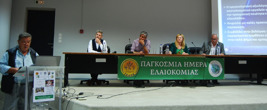 World Olive Day speakers, one standing at a podium, others sitting behind a table on a stage