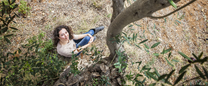 Eleni Zotou looking up from under an olive tree (viewed from above)