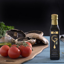 a black and gold bottle of Gold Elasion extra virgin olive oil next to tomatoes and portobellow mushrooms that rest on a wooden cutting board
