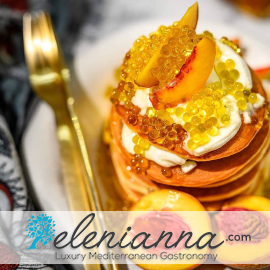 Lemon pearls atop a stack of small pancakes with fruit and cream above the words