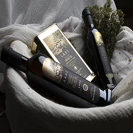 2 bottles and 1 tin of Laas extra virgin olive oil on a white cloth in a basket