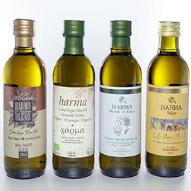 4 glass bottles of Harma extra virgin olive oil lined up next to each other