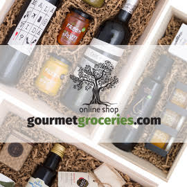 gourmetgroceries.com words and tree logo on top of a gift box with various bottles and jars