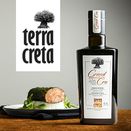 a bottle of Grand Cru extra virgin olive oil, with a plate of gourmet delicacies to its left and the name and logo of Terra Creta above the plate
