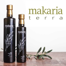 large and small Makaria Terra olive oil bottles with an olive branch design on the dark bottle, next to a small olive branch on a table