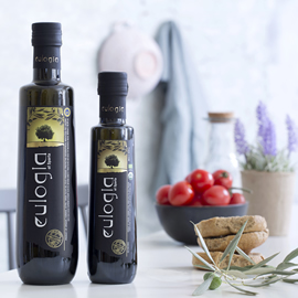 large and small dark bottles of Eulogia extra virgin olive oil on a white table with olive leaves, rusks, and a white bowl of small tomatoes