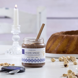 a jar of sesame spread with cocoa and hazelnut, with hazelnuts, cake, and a lit white candle on a white table
