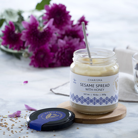 a jar of sesame spread with honey with purple flowers on the table behind it