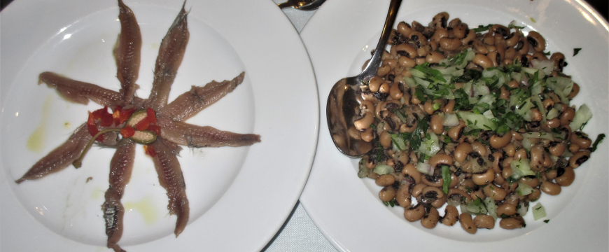 two round white plates next to each other, one with small preserved fish fillets arranged like rays, the other with a black eyed pea salad