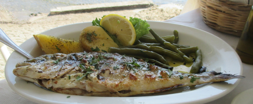 Grilled whole fish, green beans, lemon, and potato pieces with olive oil on a white oval plate