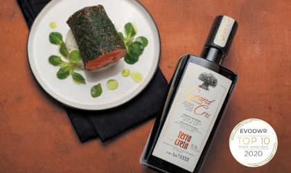 a bottle of Terra Creta Grand Cru extra virgin olive oil between a plate of delicacies and the EVOOWR Top 10 badge