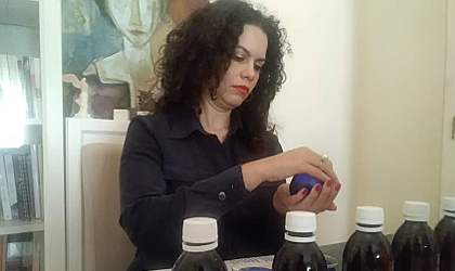 Irini Kokolaki preparing to taste olive oil from a blue glass