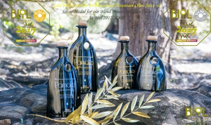 Four Pamako olive oil bottles in a forest, with logos and words about BIOL prizes they won