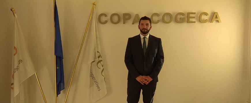Vasilis Pyrgiotis standing in front of a Copa-Cogeca sign, next to three flags