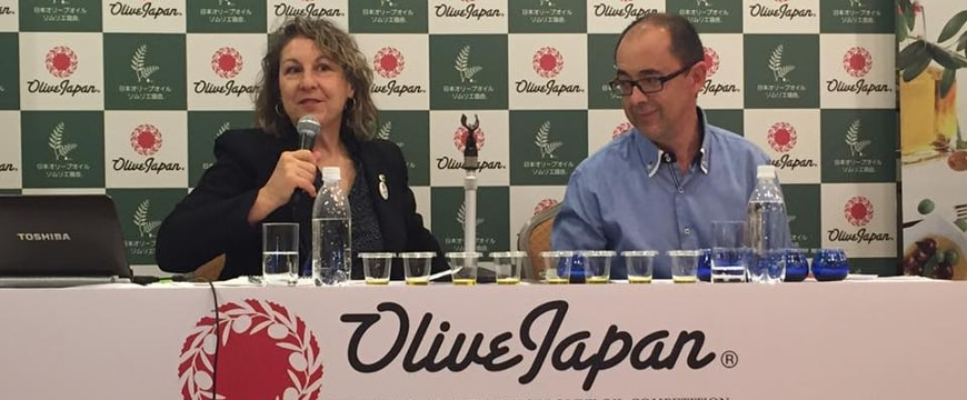 Alexandra Devarenne sitting at a table next to a man, with Olive Japan on a sign hanging down in front of the table