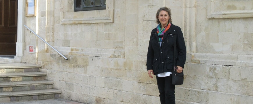 Alexandra Devarenne standing in front of a church wall outdoors in Heraklion, Crete