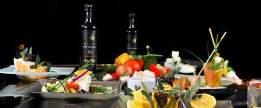 colorful foods on plates and dark bottles of ACAIA olive oil