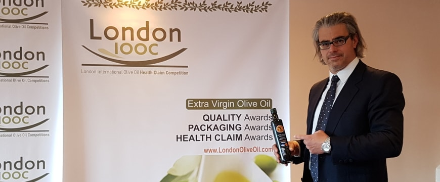 Pantelis Fanourgakis with his olive oil in front of a backdrop about the London Olive Oil Competitions