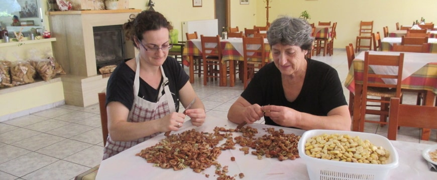 Two women peeling fava beans at a table at Iliomanolis Taverna in Crete