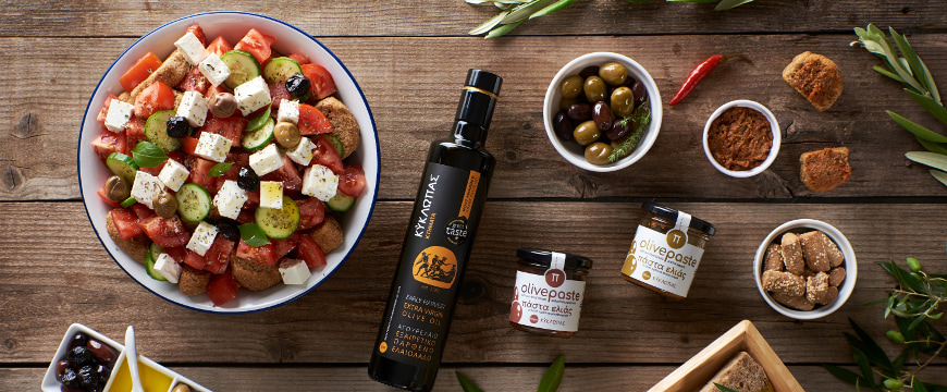 Kyklopas olive oil and olive paste near a colorful salad, all viewed from above