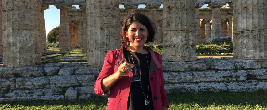 Cristina Stribacu holding her EVO IOOC award, standing in front of the base and columns of an ancient temple