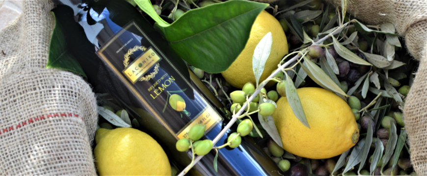 a bottle of Laconiko lemon infused olive oil, lying on its side in the midst of harvested olives and lemons