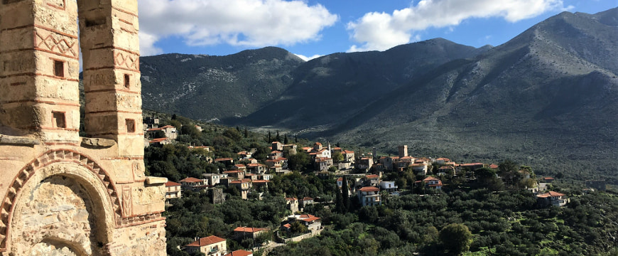 looking down on the Liokareas olive groves in Mani from a spot next to a church, with mountains on the far side of a valley