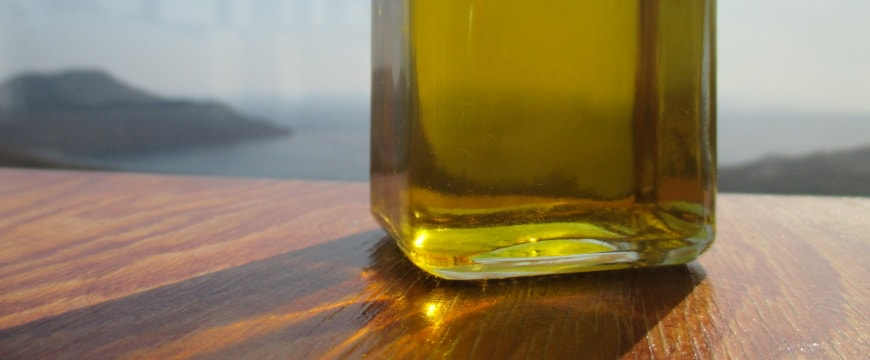 Part of a clear bottle of olive oil on a wooden table with sea and land view in the background