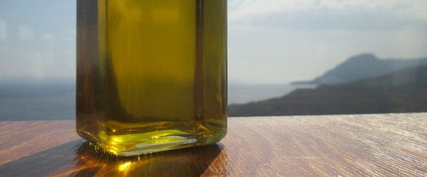clear glass bottle with olive oil, view of sea and hills in background