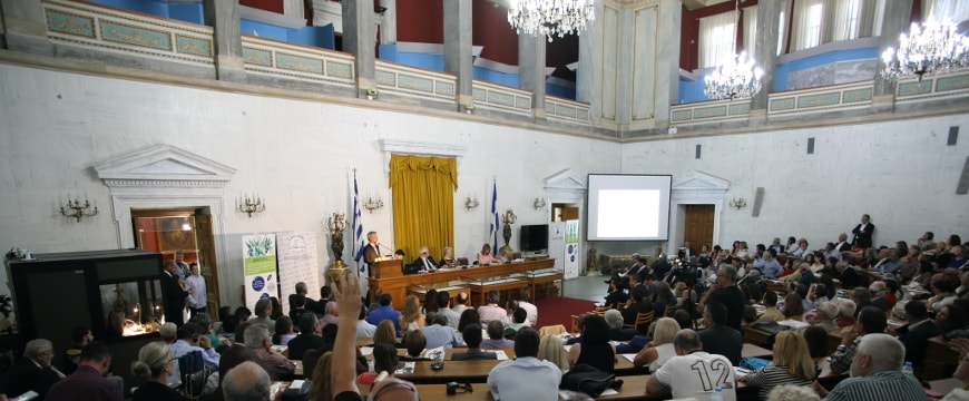 The Old Parliament auditorium in Athens, full of people, with presenters at a table and podium in front