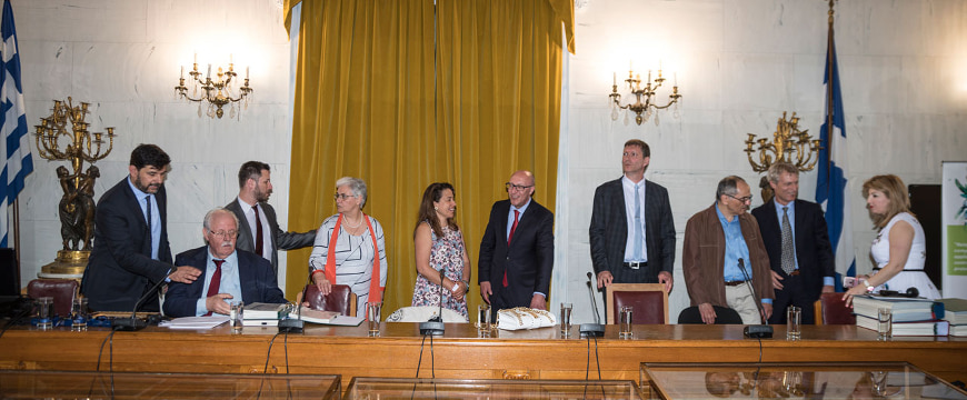 The speakers at the Olympia Awards ceremony standing behind a table in the Old Parliament in Athens