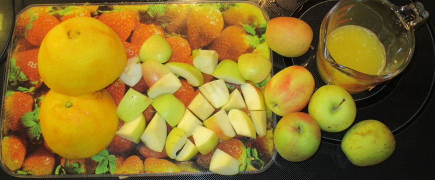 orange peel and apple chunks on a cutting board, small apples and a glass measuring cup half full of orange juice