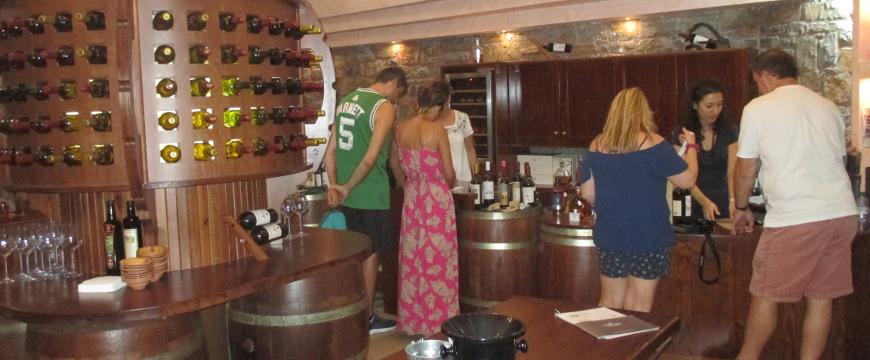 The Toplou wine tasting room, with bottles of wine on display and visitors talking with staff about wine choices