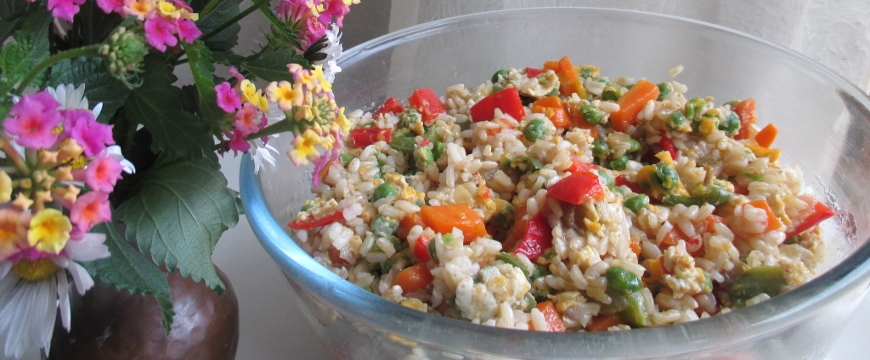 vegetable fried rice in a glass bowl next to wildflowers