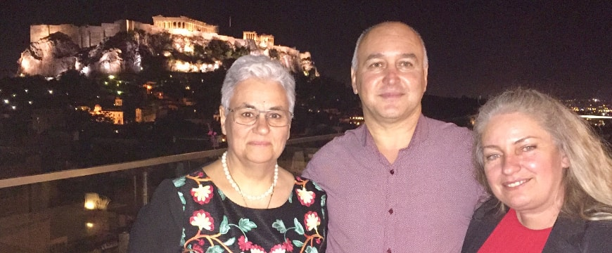 Professor Magda Tsolaki, Yannis and Evi Prodromou, with the Acropolis in the background, at night