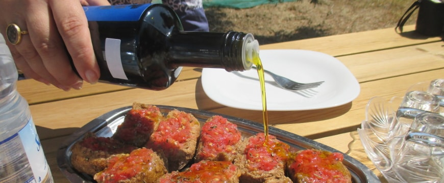 olive oil being poured onto crushed tomato on rusks