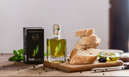 a small clear glass bottle of Cretanthos olive oil between its black box and a stack of sliced bakery bread on a cutting board