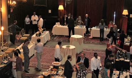 A large, high-ceilinged, wood paneled room at Harvard club with people standing around near white-clothed tables with olive oil