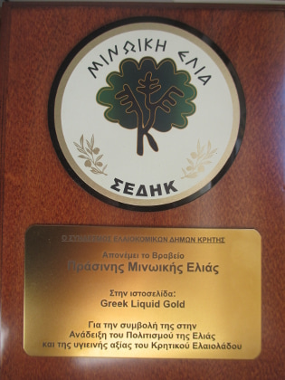 A plaque with a stylized olive tree and text about the award for the Greek Liquid Gold website