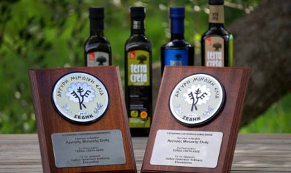 Terra Creta's latest awards in front of some bottles of their olive oil