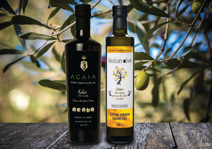 ACAIA and Aeolian Olive bottles of olive oil next to each other, in front of an olive tree