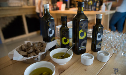 Anoskeli olive oil bottles, bowls of olive oil, rusks, and small tasting glasses