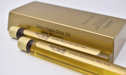 2 vials of Eureka olive oil next to a gold box