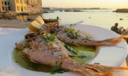Whole baked fish on plate with olive oil at a restaurant, sea and old buildings in the background