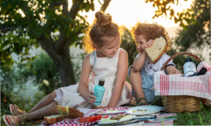two young children having a picnic outdoors, with one of them holding a bottle of Goutis Estate olive oil