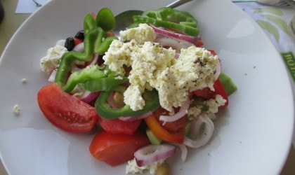 Greek salad with soft white mizithra cheese on top of the vegetables