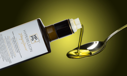 a bottle of Hypereleon extra virgin olive oil, with olive olive oil from it being poured into a spoon