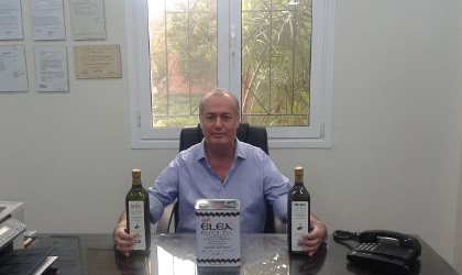 Loutraki Oil Company's Athanasios Katsetos at his desk, with Elea olive oil containers on it